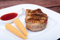 Grilled pork chop with Cranberry sauce and Mini Corn cob preserved on plate on wooden board Royalty Free Stock Photo