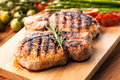 Grilled pork chop with rosemary leaf on wooden board Royalty Free Stock Photo