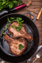 Grilled pork chop with spices in a frying pan. Royalty Free Stock Photo