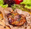 Grilled pork chop with spices and herbs on parchment paper Royalty Free Stock Photo