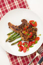 Grilled pork chops and asparagus served with fried grape tomatoes salad and pesto sauce Stock Photography