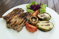 Grilled pork with grilled vegetables on white plate Royalty Free Stock Photos