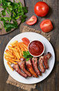 Grilled pork ribs, vegetables, potato fries and tomato sauce Royalty Free Stock Photo