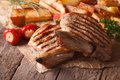 Grilled pork steak with potatoes and vegetables close up on pape Royalty Free Stock Photo