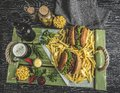 Grilled pulled beef sandwich, burger, french fries, sauce, dark beer, corn on a wooden tray Royalty Free Stock Photo