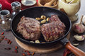 Grilled rib eye steak composition on grill iron pan on wooden background