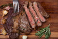 Grilled rib-eye steak of marble beef closeup with spices on a wooden Board. Juicy steak medium rare, sliced and ready to eat Royalty Free Stock Photo