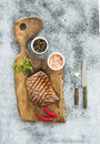 Grilled ribeye beef steak with herbs and spices on walnut cutting board over grunge grey background Royalty Free Stock Photo