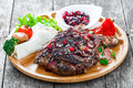Grilled Ribeye Steak on bone with berry sauce, fresh salad and grilled vegetables on cutting board on wooden background