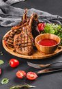 Grilled Ribeye Steak on bone and vegetables with fresh salad and bbq sauce on cutting board over black stone background. Hot Meat Royalty Free Stock Photo