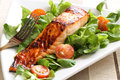 Grilled salmon with a honey glaze on bed of lambs lettuce Royalty Free Stock Photos