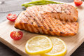 Grilled salmon and lemon, asparagus, tomato on the wooden table Royalty Free Stock Photo