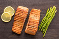 Grilled salmon with lemon, asparagus on the wooden background Royalty Free Stock Photo