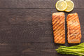 Grilled salmon with lemon, asparagus on wooden background Royalty Free Stock Photo