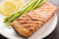 Grilled salmon and lemon, asparagus, on the wooden table Royalty Free Stock Photo