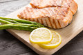 Grilled salmon with lemon, asparagus on the wooden table Royalty Free Stock Photo