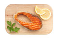 Grilled salmon with lemon slices and parsley on cutting board isolated white background Royalty Free Stock Photo