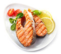 Grilled salmon steak slices on a white plate Royalty Free Stock Images