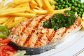 Grilled salmon steak with veg Royalty Free Stock Image