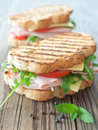 Grilled sandwiches deli with ham and cheese on top of a chopping board Stock Photos