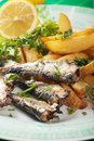 Grilled sardine fish with potato wedges fried Royalty Free Stock Images