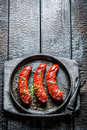 Grilled sausage with fresh herbs on hot barbecue dish burnt table Royalty Free Stock Photography