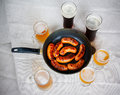 Grilled sausages and beer glasses on table. Top view Royalty Free Stock Photo