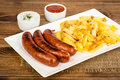 Grilled sausages and fried potatoes on the white plate on the rustic surface wooden Royalty Free Stock Photos