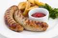Grilled sausages with potatoes and gravy Royalty Free Stock Photos