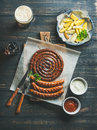Grilled sausages, roasted potato and dark beer over wooden background Royalty Free Stock Photo