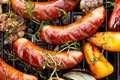 Grilled sausages and vegetables with addition spices and fresh herbs on a grill plate Royalty Free Stock Photo