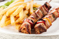 Grilled shashlik with chips on plate Royalty Free Stock Image