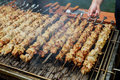 Grilled shish kebab on metal skewer. Chef hands cooking roasted meat barbecue with lots of smoke. Royalty Free Stock Photo