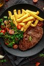 Grilled sirloin steak with potato fries and vegetables, tomato salad in a black plate. rustic table Royalty Free Stock Photo