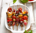 Grilled skewers of vegetables and meat in a herb marinade on white plate Royalty Free Stock Photo