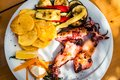 Grilled squid with potato chips, vegetables on a white plate Royalty Free Stock Photo
