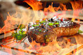 Grilled steak with flames in background Royalty Free Stock Image
