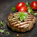 Grilled steak with herbs and tomatoes on dark slate Stock Image