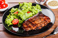 Grilled steak meat with fresh vegetable salad and tomatoes on black plate, wooden background. Royalty Free Stock Photo