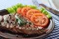 Grilled steak on plate with tomatoes spices and rosemary closeup Royalty Free Stock Photography