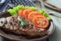 Grilled steak on plate with tomatoes spices and rosemary closeup Royalty Free Stock Image