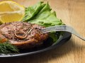 Grilled steak with salad and lemon on black plate with fork at wood background Royalty Free Stock Images