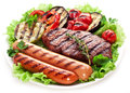 Grilled steak sausages and vegetables over lettuce leaves Stock Photo