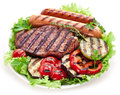 Grilled steak sausages and vegetables over lettuce leaves Stock Photos