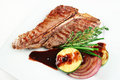 Grilled t bone with vegetables and red sauce on white plate Stock Image