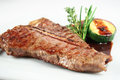 Grilled t bone with vegetables and red sauce on white plate Royalty Free Stock Photo