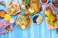Grilled vegetables, shrimp, fruit on a wooden plate and sausages, juice and salad on a blue background. Summer dinner. Free space Royalty Free Stock Photo