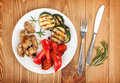 Grilled vegetables and silverware over wooden table background view from above Royalty Free Stock Photos