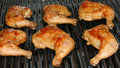 Grilling chicken leg quarters Stock Images