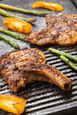 Grilling pork chops juicy are grilled on griddle with asparagus and bell pepper backyard for summer picnic Stock Images